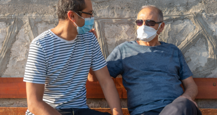 two men sitting on a bench masks on
