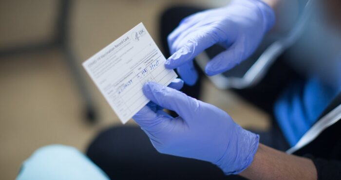 Person holding COVID vaccination card