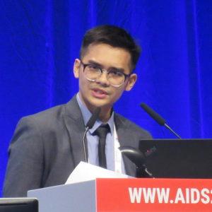 Photo of Akarin Hiransuthikul speaking at podium