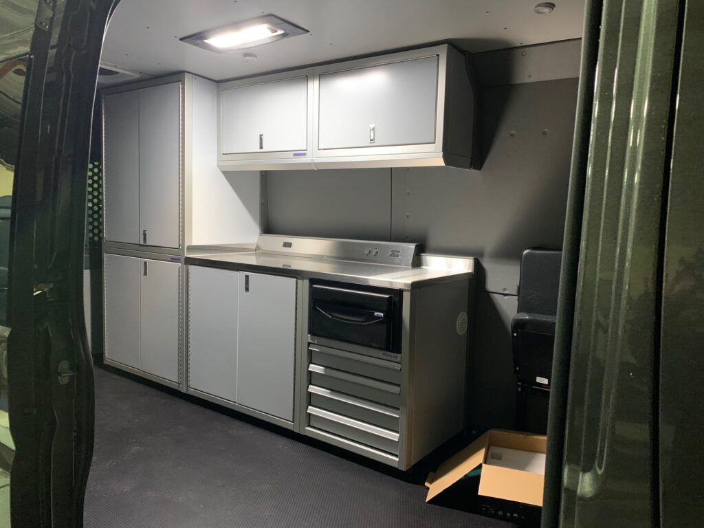 This photo shows the interior of a van. It has light gray cabinets and a cabin light.