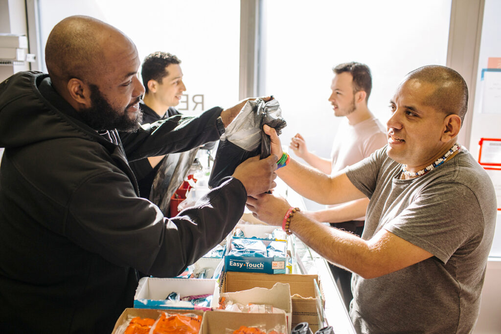 An image of two people providing harm reduction supplies to two people.
