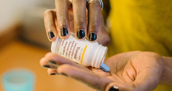 A person dispenses a blue pill from a medication bottle into their hand