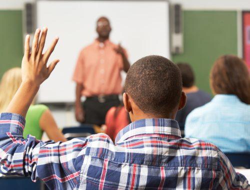 person raising hand classroom