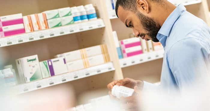 Pharmacist looking at medication bottle