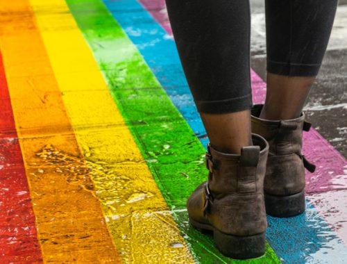 Person walking on rainbow sidewalk